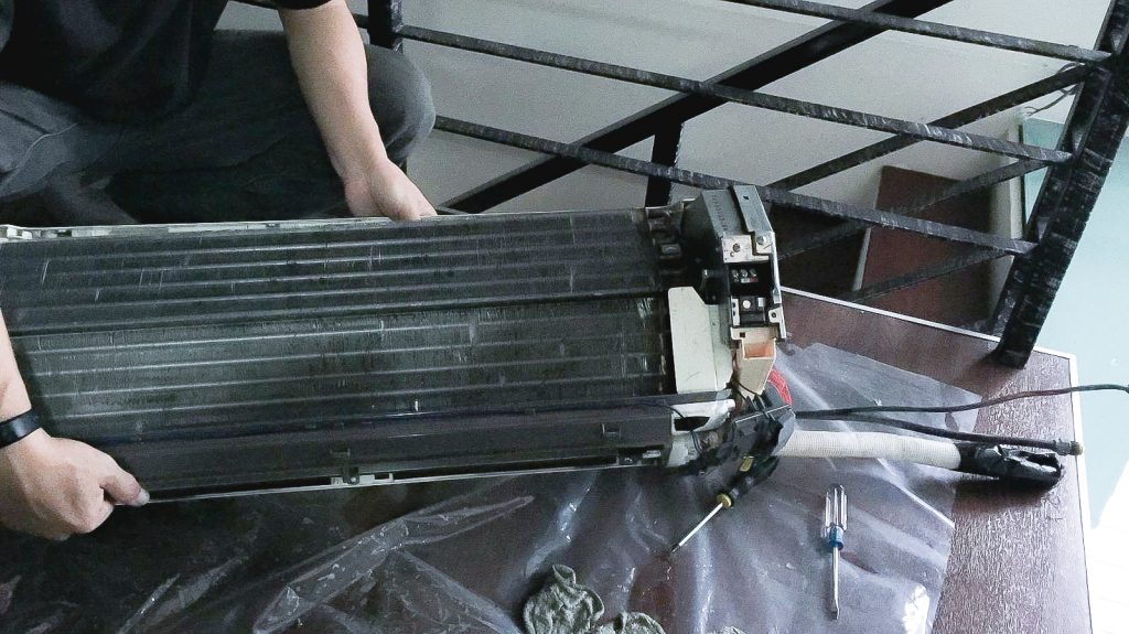 technician cleaning condenser coil
